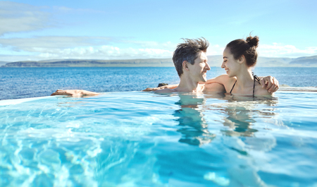 woman bath: Young cheerful girl with man swimming in water of pool looking each other on background of sea, Iceland, West Fjords.