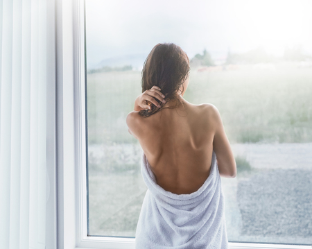 female in douche: young slender woman stands at a window wrapped in a towel. woman after the shower, she has a back open, she looks out the window. Beautiful young woman after shower standing near window at home Stock Photo