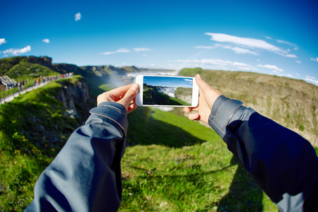 Hands holding a smartphone with a picture of the landscape - famous Gullfoss waterfall in southern Iceland. treking in Iceland. Travel and landscape photography concept