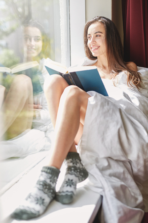 young smiling woman sits on a windowsill with old book. the woman is sitting without clothes, wrapped in a blanket Stock Photo