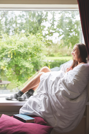 young smiling woman sits on a windowsill. the woman is sitting without clothes, wrapped in a blanket and looking in the garden Stock Photo