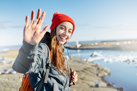 portrait of happy young smiling woman in warm clothing and knitted red hat with orange backpack in Ice Lagoon in Iceland with background of sea and sky. a woman is waving a hand with a happy look and a smile
