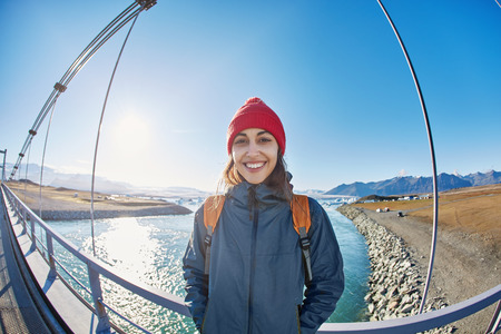 Cheerful woman wearing in red cup walks on the brige in Jokulsarlon Ice Lagoon, Iceland