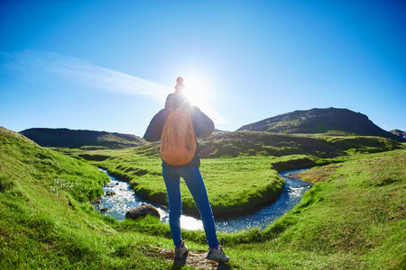 woman traveler with small orange backpack on a walk in the Valley of the river of Hveragerdi Iceland. Hiking Tour of Reykjadalur Hot Springs