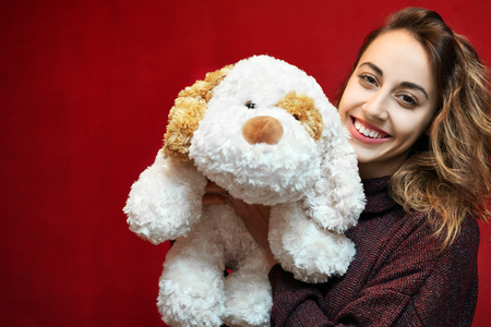 happy beautiful smiling woman with a big toy dog on a red wall background. Valentines day, mothers day, birthday and a gift
