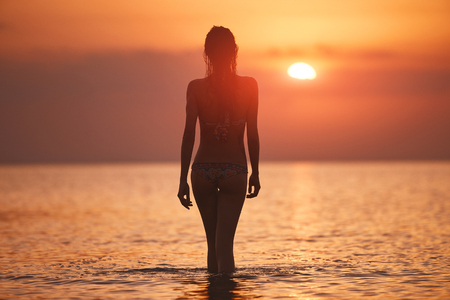 silhouette of a beautiful sexual girl against the sea and sunset. happy woman enjoying summer vacation