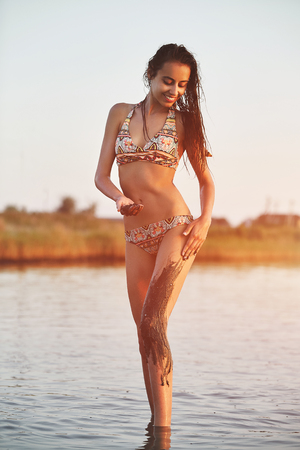 beautiful sexual smiling girl in the sea at sunset paints itself with medicinal mud. Natural spa. happy woman enjoying summer vacation Stock fotó