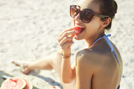 young beautiful woman eats watermelon on the beach at hot summer day, back view.