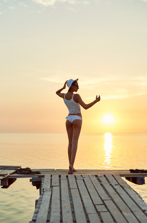 beautiful sexual woman in white hat and bikini stands on the wooden pier on the beach against the sea and sky. happy woman enjoying summer vacation, back view