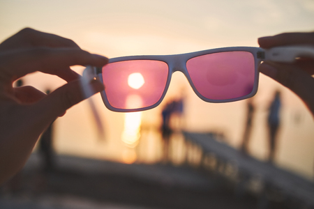 view of the sun, sea and sky through pink sunglasses at sunset. a look at the world through rose-colored glasses, the idea of illusory and naivety