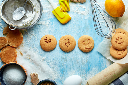 round cookies with cheerful emotions, faces with emotions on a blue wooden backdrop