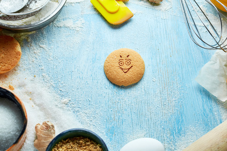 round cookie with cheerful emotion, face with emotion on a blue wooden backdrop