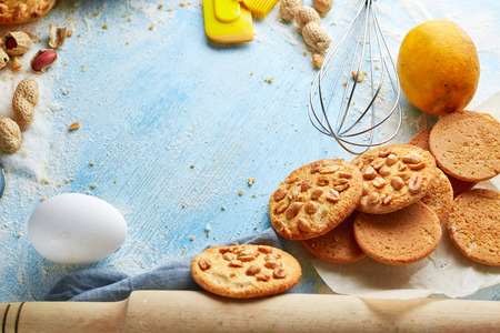 top view of product set for cooking cookies, kitchenware and several round cookies with peanuts on the blue wooden background