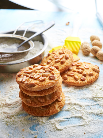 top view of product set for cooking cookies, kitchenware and several round cookies with peanuts on scattered flour on a blue wooden table 스톡 콘텐츠
