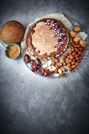 top view with copyspace of Chocolate raw vegan cake with different nuts, dates, carob zlage and currant berries on the paper for baking and droduct set for cooking on the gray concrete table. Vegan and healthy eating concept. Stock Photo