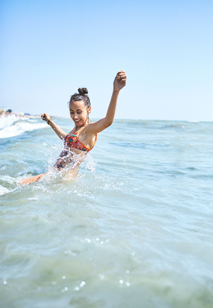 happy smiling woman swims in the sea and splashed on the waves Foto de archivo