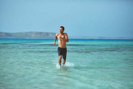 strong athletic man runs on the beach along the sea front. vacation and travel photography concept