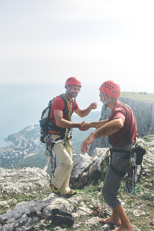 two man rock climbers climbed on the cliff. happy climbers on the top of the mountain. friends hug and congratulate each other on a successful climb