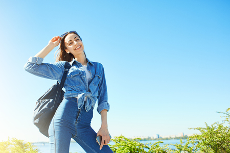 portrait of a young smiling attractive woman in jeans clothes with small city backpack at sunny day on the blue sky and river background. joyful woman posing in city scape. Stok Fotoğraf