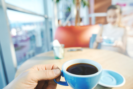 A man's hand holding a blue cup of coffee with woman on background. A couple sitting in coffee shop and having coffee