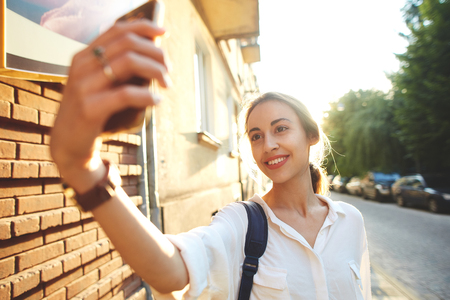 portrait of happy smiling woman walking on the street. wman making selfie by phone camera on the street at sunset, Ukraine, Lviv.