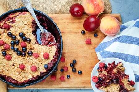 Food background. crumble with blueberries in the black cast-iron frying pan on the wooden cutting board with fruits and napkin. Top view