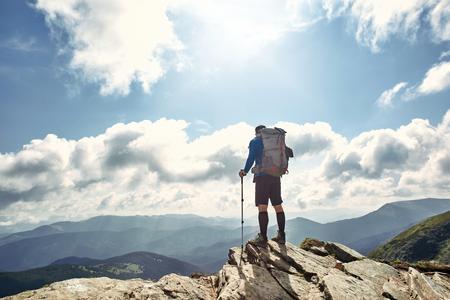 Active hiker enjoying panoramic view of sunrise in mountains, travel and outdoor adventure concept. Carpathians, Ukraine Foto de archivo