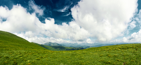 panoramic view of Chornohora mountain ridge and beautiful cluody sky from slopes of Hoverla mountain. mountain slope in low lying cloud with the evergreen conifers shrouded in mist in a scenic landscape view