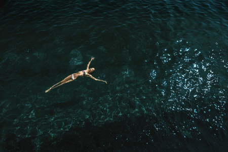 aerial view of a beautiful sexy slim woman floating and reraxing in the deep blue sea. relaxed woman floating on transparent turquoise sea. Summer seascape with girl and azure water