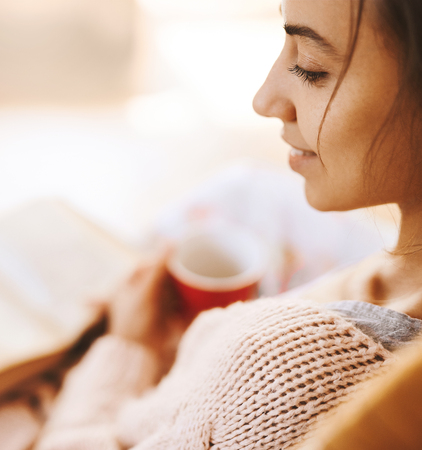 portrait of woman in a wicker chair with old book and cup of coffee. Woman wearing in cozy knitted pink sweater, selective focus, focus on the eye