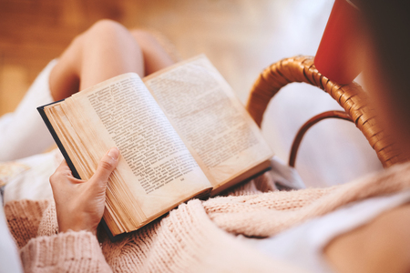Soft photo of woman in a wicker chair with old book and cup of coffee. Woman wearing in cozy knitted pink sweater and white knee socks. top view, focus on the book.