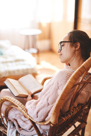 Soft photo of woman in a wicker chair with old book and cup of coffee. Woman wearing in cozy knitted pink sweater and white knee socks.