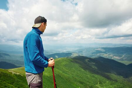 Active male hiker enjoying view of beautiful cloudy sky in mountains, travel and outdoor adventure concept. Carpathians, Ukraine