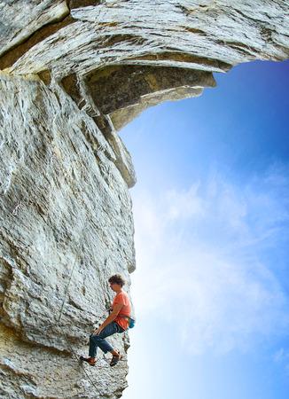 Weitwinkelansicht des männlichen Kletterers. Kletterer klettert auf eine Felswand. Mann ruht an einem Seil hängen Standard-Bild