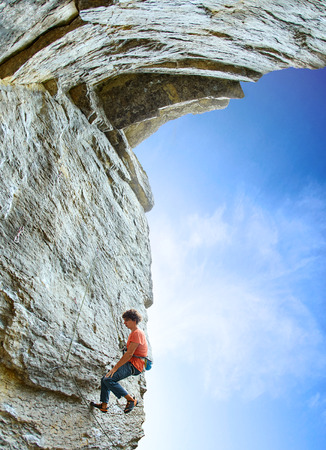 wide angle view of male rock climber. rock climber climbs on a rocky wall. man resting hanging on a rope