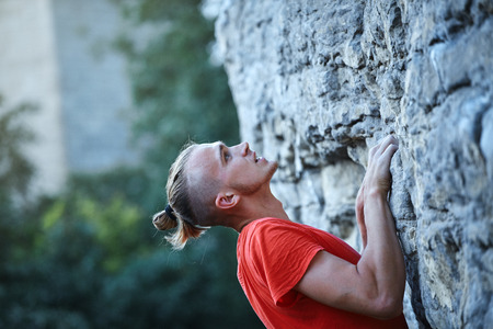 man rock climber with long hair. close up side view of young man rock climber in bright red t-shirt climbing the challenging route on the cliff. rock climber climbs on a rocky wall. man making hard move Imagens