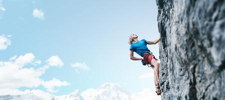 Mann Kletterer mit langen Haaren. Seitenansicht des jungen Kletterers in leuchtend roten Shorts, der die anspruchsvolle Route auf der Klippe auf dem Hintergrund des blauen Himmels klettert. Kletterer klettert auf eine felsige Wand.