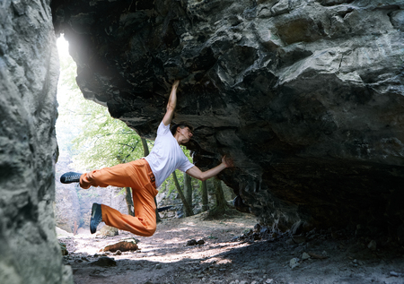 man rock climber in bright orange pants climbing on the overhanging cliff in forest. man making hard dynamic move. Extreme sport concept