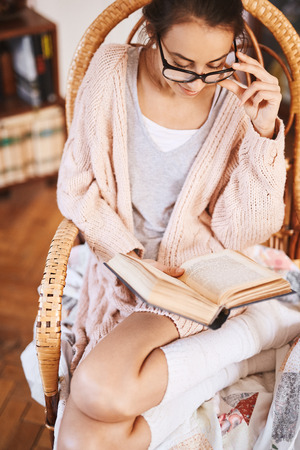 Young woman in big glasses is reading a book at home. Soft photo of woman in a wicker chair with old book. Woman wearing in cozy knitted pink sweater and white knee socks. Stock Photo