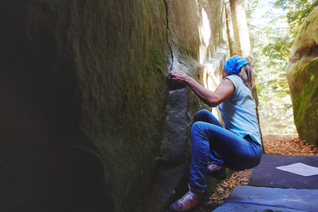 A strong woman rock climber climbing a rock outdoors in forest. Athletes are bouldering outdoors.
