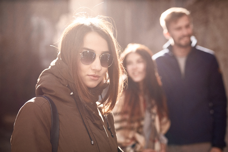 sad lonely woman in black sunglasses on the happy couple background. third wheel. love triangle. abandoned lonely woman