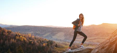 vrouw wandelaar met rugzak staande op de rand van de klif tegen de achtergrond van zonsopgang.