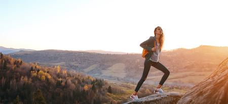 woman hiker with backpack standing on edge of cliff against background of sunrise.