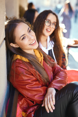 two young bright girls spending time together, walking city and having fun. joyful Women in bright colored hoodies sitting at the table in street cafe, talking and laughing Stock Photo