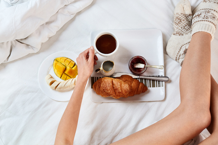 top view of a woman in wool knitted socks sitting on the bed with breakfast. a plate with croissants, jam and fruits and cup of coffee for breakfast in bed.