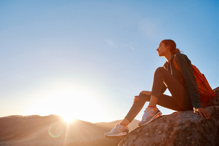 pretty woman hiker with small orange backpack sits on edge of cliff against background of sunrise Zdjęcie Seryjne