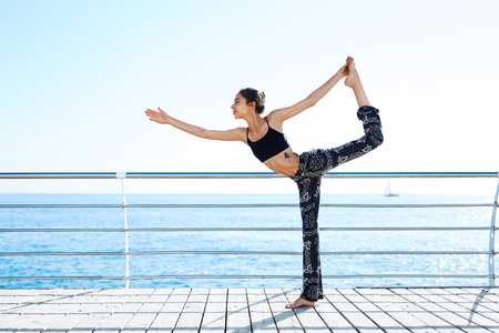 Photo of young sports woman make yoga exercises on seaside. Side view of athletic lady doing wide stance forward bend pose on the beach. Prasarita Padottanasana Yoga Pose. Healthy lifestyle, morning exercises, meditation. 版權商用圖片