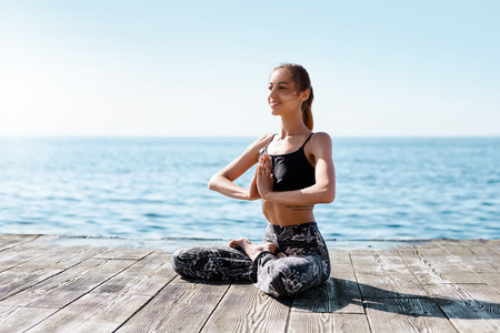 Beautiful young woman sitting in lotus pose, doing namaste mudra gesture at the beach with sea background. Feeling so comfortable and relax. Slim model practice morning meditatione on a wooden pier. Healthy Concept.