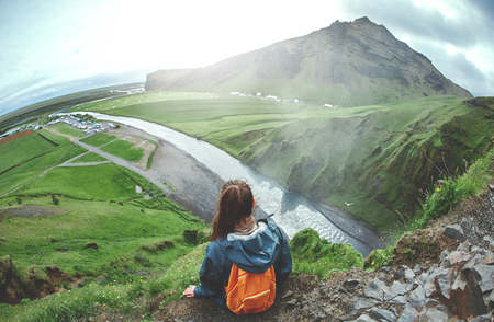 woman traveler in waterproof clothing sits on the cliff on background of Skogafoss waterfall in Iceland. View from above