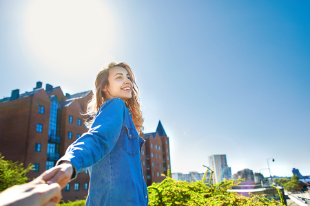 portrait of a young smiling attractive woman in jeans clothes at sunny day on the blue sky background. happy woman gives a hand to someone like follow me . first person view